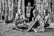 Children of the El Molo tribe sitting in front of a thatched hut, black and white, Lake Turkana, Loiyangalani,Kenya, Africa
