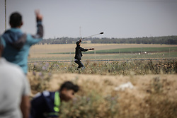 May 19, 2017 - Gaza, Gaza - A Palestinian protester uses a sling to hurl stones at Israeli troops during clashes following a protest against the blockade on Gaza, near the border between Israel and  Gaza Strip May 19, 2017. (Credit Image: © Nidal Alwaheidi/Pacific Press via ZUMA Wire)