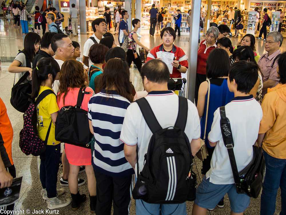14 AUGUST 2013 - HONG KONG:  A Hong Kong travel official briefs passengers on theird delay because of Severe Typhoon Utor at Hong Kong International Airport. Dozens of flights were delayed at one of the busiest airports in Asia and Hong Kong raised their alert to level 8, the highest, and closed schools and many businesses because of Severe Typhoon Utor. The storm passed within 260 kilometers of Hong Kong before making landfall in mainland China. Severe Typhoon Utor (known in the Philippines as Typhoon Labuyo) is an active tropical cyclone located over the South China Sea. The eleventh named storm and second typhoon of the 2013 typhoon season, Utor formed from a tropical depression on August 8. The depression was upgraded to Tropical Storm Utor the following day, and to typhoon intensity just a few hours afterwards. The Philippines, which bore the brunt of the storm, reported 1 dead in a mudslide and 23 fishermen missing at sea.  PHOTO BY JACK KURTZ