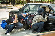 02 DECEMBER 2013 - BANGKOK, THAILAND:  Rioters take shelter behind a car wrecked during riots in Bangkok. Anti-government protestors and Thai police continued to face off Monday for a second day. Police used tear gas, water cannons and rubber bullets against protestors who charged their positions near the barriers on Chamai Maruchet bridge on Phitsanulok Road, which leads to the Government House.    PHOTO BY JACK KURTZ