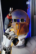 Robonaut, with an acrylic head, holds a drill with socket attachment at the Johnson Space Center, Houston. That NASA's teleoperated humanoid-type robot, called Robonaut, has no legs is by design, because in space, says project leader Robert Ambrose, an astronaut's legs can be a big impediment to fulfilling the mission of a spacewalk. The latest version of Robonaut has two arms, a Kevlar and nylon suit, updated stereo eyes, and is getting heat sensing capability. Possibly the most significant change is the move from total teleoperation to some level of autonomy.