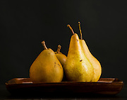 Illustrative photography presenting multiple views of four pears on a plate