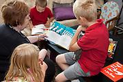 Grandma reading to grandchildren age 70, 4, 6 and 8. Zawady Central Poland