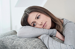 Portrait of pensive young woman on couch at home