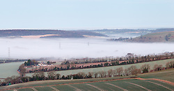 © Licensed to London News Pictures. 21/01/2014. Butser Hill, Petersfield, Hampshire, UK. Low cloud blankets fields through Hampshire at dawn this morning, 21st January 2014. Photo credit : Rob Arnold/LNP