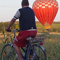 A biker watches a balloon landing during the Velence Lake International Hot Air Balloon Festival in Agard, Slovakia on September 10, 2011. ATTILA VOLGYI