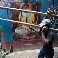 A man carries a bamboo ladder through the streets of Old Dhaka, Bangladesh and passes by a Hindu temple