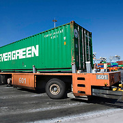 Nederland Zuid-Holland Rotterdam  27-08-2009 20090827 Foto: David Rozing .Serie over logistieke sector.ECT Delta terminal in de haven van Rotterdam. Robotgestuurde wagens vervoeren de containers op de terminal. Evergreen container onderweg naar een zeeschip. .ECT,European Container Terminals, at the Port of Rotterdam. Europe's biggest and most advanced container terminal operator, handling close to three- quarters of all containers passing through the Port of Rotterdam. ECT is a member of the Hutchison Port Holdings group (HPH), the world biggest container stevedore with terminals on every Continent. At the ECT Delta Terminal unmanned, automated guided vehicles  so called AGVs  transport the containers between ship and stack. In the stack, unmanned automated stacking cranes ( ASCs ) ensure that the containers are always stacked in the correct place. Terminal operations are highly automated for discharging and loading large volumes...Holland, The Netherlands, dutch, Pays Bas, Europe .Foto: David Rozing