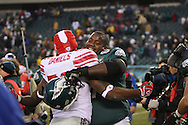 PHILADELPHIA - DECEMBER 9: Max Jean-Gilles #62 of the Philadelphia Eagles embraces Tank Daniels #52 of The New York Giants after the game on December 9, 2007 at Lincoln Financial Field in Philadelphia, Pennsylvania. The Giants won 16-13.