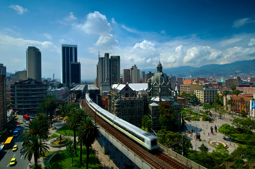 The elevated Medellin Metro is in motion as it glides out of Parque Berrio Metro Station in front of Plaza Botero.  Plaza Botero was named after Medellin's native son and Colombia's most famous artist, Fernando Botero.  The striped art nouveau Palace of Culture and downtown office buildings can be seen in the background.