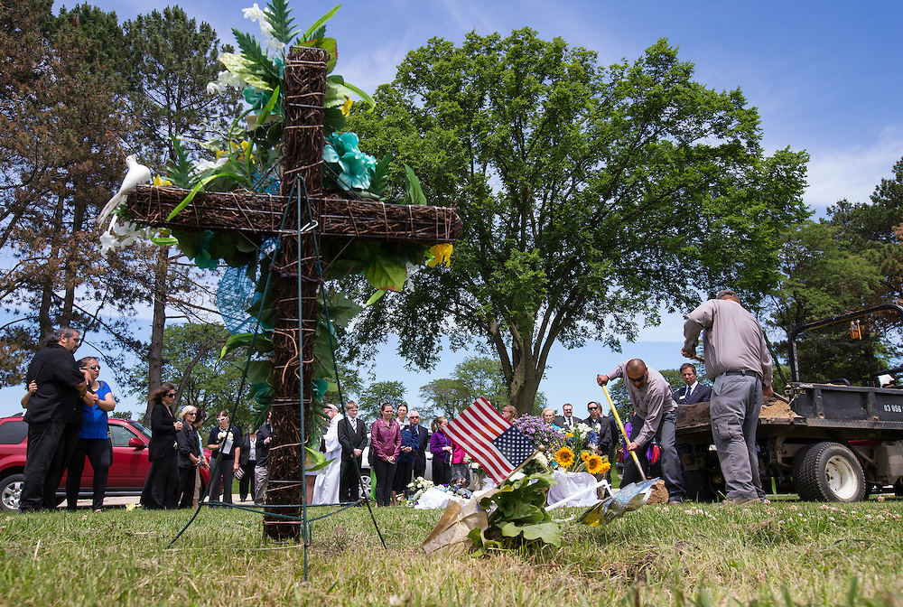 """Workers shovel dirt on to the casket of an abandoned newborn baby boy during a burial service at All Saints Cemetery in Des Plaines, Illinois, United States, June 19, 2015. More than a year after he was found dead in a plastic shopping bag on a Chicago sidewalk, the baby boy was buried by a non-profit group """"Rest in His Arms"""" after abandoned by his teenage mother, who is charged with murder.  REUTERS/Jim Young"""