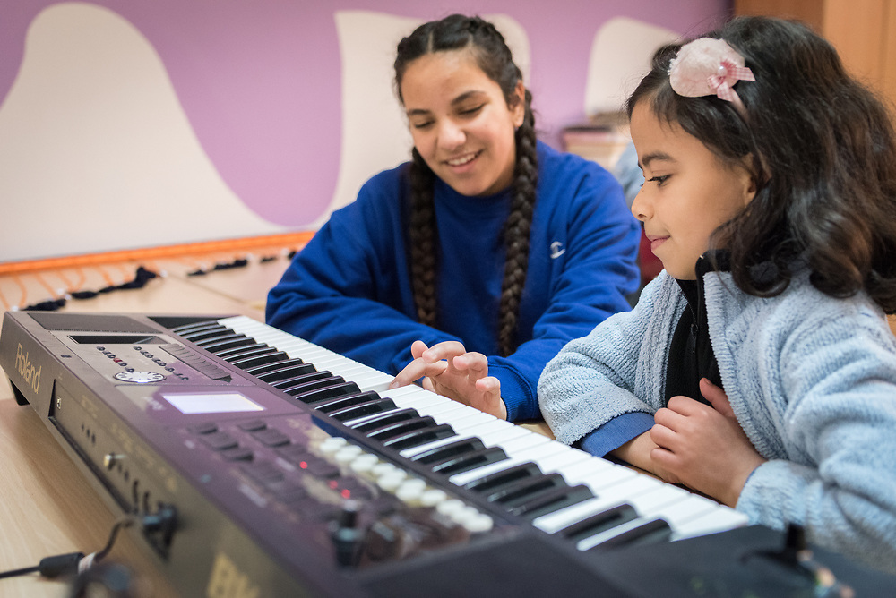 18 February 2020, Amman, Jordan: 15-year-old Rena Almaharmeh (left) receives instruction from ten-year-old Saja (right) on how to play the keyboard in the Talent Room of Rufaida Al Aslamieh Primary Mixed School in the Sahab district. The school serves more than 1,000 students from kindergarten up to 10th grade, most of them girls from Jordan but also some from Syria and other countries, and, in the lower grades, also boys. With support from the Lutheran World Federation, the school has refurbished its rooms and buildings and introduced a 'Talent Room' in order to nurture the children's creativity. This type of learning environment is otherwise rare in Jordanian public shools.