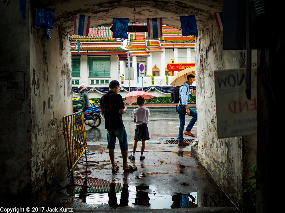 27 MARCH 2017 - BANGKOK, THAILAND: A boy at the gate of Pom Mahakan takes shelter under an umbrella during a rain shower in Bangkok. The final evictions of the remaining families in Pom Mahakan, a slum community in a 19th century fort in Bangkok, have started. City officials are moving the residents out of the fort. NGOs and historic preservation organizations protested the city's action but city officials did not relent and started evicting the remaining families in early March.                 PHOTO BY JACK KURTZ
