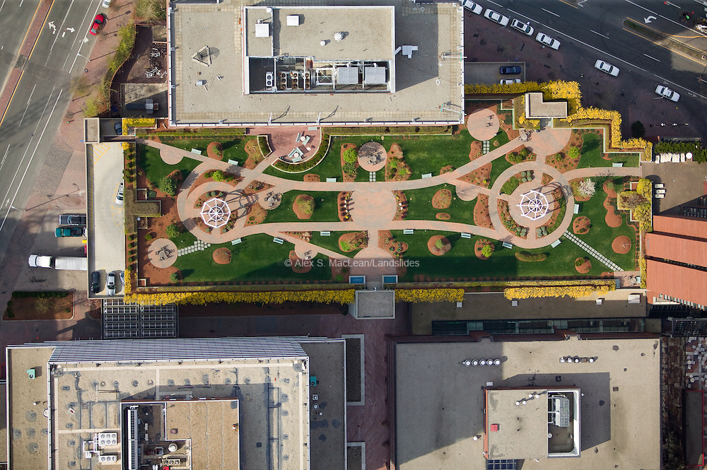 Cambridge Center Garage Roof Garden in Kendal Square<br /> <br /> Taken directly from the web:<br /> http://www.artonfile.com/html/projectnotes.lasso?code=PPI-10-06<br /> <br /> Project Code: PPI-10-06 <br />   <br /> Architect/Artist: Martha Schwartz, Peter Walker <br /> Description: A post-modern landscape transforms the top of a parking garage into a one-acre public park. Weight restrictions influenced the design of a series of sculptural trellises and box planters that form a maze pattern on the roof. Crushed white stone covers the surface, and inlaid stepping stones provide a path for walking.<br /> <br /> A large office building connects to the parking garage, giving building occupants access to the roof-top garden.