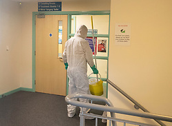 © Licensed to London News Pictures. 10/02/2020. London, UK. A worker in protective overalls and face mask is seen inside the closed County Oak Medical Centre in Brighton. It has been closed due to it's links with one of the newly diagnosed Corona Virus cases from the south coast. Earlier today four British people tested positive for the virus, having been in contact in France with a UK businessman who caught the virus in Singapore before flying to a French ski resort. .Photo credit: Peter Macdiarmid/LNP