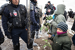 © London News Pictures. Calais, France. 07/03/16. Refugee children try to give white flowers to French riot police in an attempt to halt the demolition. French authorities are evicting and demolishing the southern half of the Calais 'Jungle' camp, which charities estimate to contain 3,500 people. . Photo credit: Rob Pinney/LNP