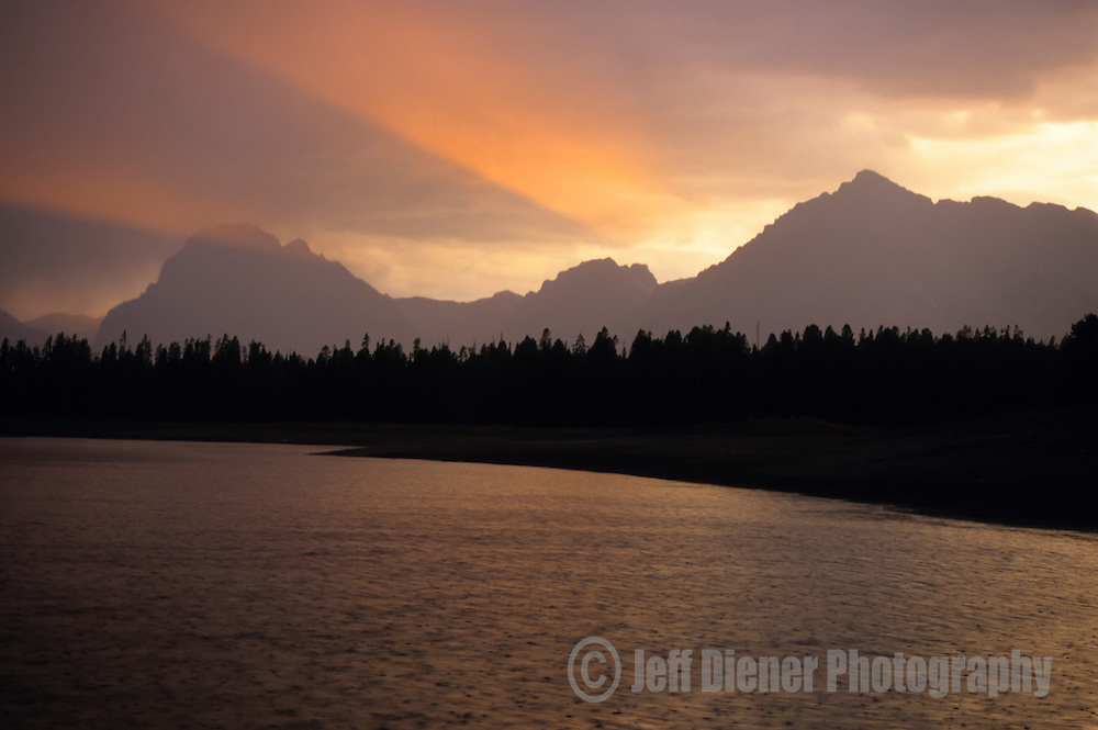 Sunset beams through the clouds over Jackson Lake in Grand Teton National Park, Wyoming.