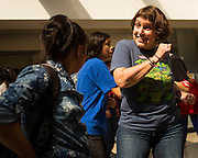 Prospect High School teacher Kim Kehres dances with students during the Santa Clara County Super Hero Dance for Special Education students at Milpitas High School in Milpitas, California, on April 18, 2014. (Stan Olszewski/SOSKIphoto)