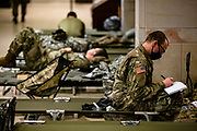 WASHINGTON, DC - JANUARY 17: National Guard soldiers rest on cots in the Visitors Center of the U.S. Capitol on January 17, 2021 in Washington, DC. After last week's riots at the U.S. Capitol Building, the FBI has warned of additional threats in the nation's capital and in all 50 states. According to reports, as many as 25,000 National Guard soldiers will be guarding the city as preparations are made for the inauguration of Joe Biden as the 46th U.S. President. (Photo by Samuel Corum/Getty Images)