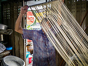 "29 DECEMBER 2018 - BANGKOK, THAILAND: A man stretches longevity noodles in his family shophouse. The family has been making traditional ""mee sua"" noodles, also called ""longevity noodles"" for three generations in their home in central Bangkok. They use a recipe brought to Thailand from China. Longevity noodles are thought to contribute to a long and healthy life and  are served on special occasions, especially Chinese New Year, which is February 4, 2019. These noodles were being made for Chinese New Year.       PHOTO BY JACK KURTZ"