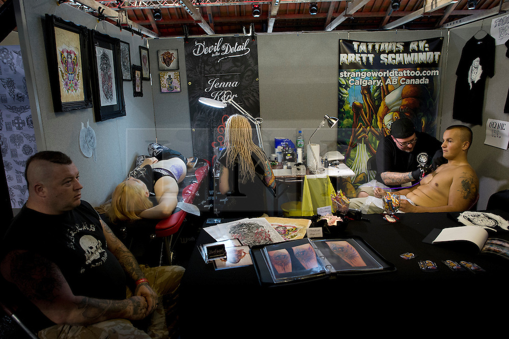 © London News PIctures. 27/09/2013. London, UK.  Tattoo artists working at the 2013 International London Tattoo Convention held at Tobacco Dock in East London. The event brings over 180 of the world's best tattoo artists to London over three days running from 27th to 29th of September.  Photo credit: Ben Cawthra/LNP