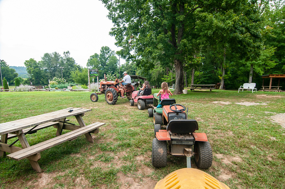 """A """"train ride"""" on a chain of lawn mowers at Christian Way Farm in Hopkinsville, Kentucky on Friday, August 11, 2017. Copyright 2017 Jason Barnette"""
