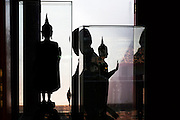 A visitor passes ancient buddha statues, Songkhla Museum, Songkhla, Thailand