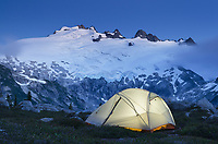 Tent illuminated during twilight at backcountry camp near Middle Lakes, Mount Challenger seen in the distance. North Cascades National Park Washington