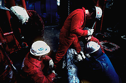 Stock photo of four workers fixing a pipe on an oil rig