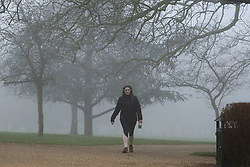 © Licensed to London News Pictures. 03/03/2021. London, UK. A woman walking in Finsbury Park, north London on a foggy morning. The Met Office has issued a yellow weather warning for fog in some parts of south east England with low visibility. Photo credit: Dinendra Haria/LNP