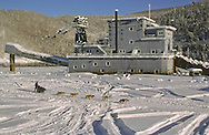 Musher and sled dogs drive in fronot of a dredge in Dawson City, Yukon<br /> <br /> NOT IN YOUR BUDGET? Contact Cathie for a price specific to your project.