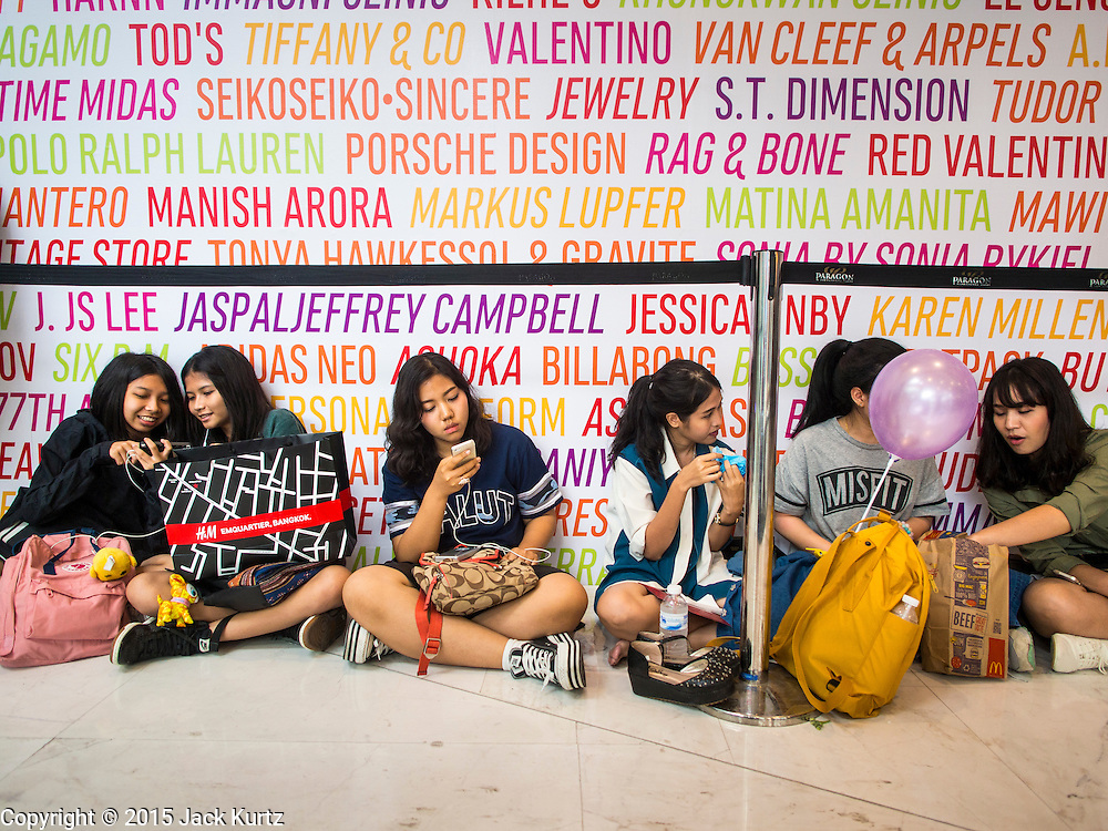 """27 MARCH 2015 - BANGKOK, THAILAND: Shoppers wait for the Style Nanda store to open in """"EmQuartier,"""" a new shopping mall in Bangkok. """"EmQuartier"""" is across Sukhumvit Rd from Emporium. Both malls have the same corporate owner, The Mall Group, which reportedly spent 20Billion Thai Baht (about $600 million US) on the new mall and renovating the existing Emporium. EmQuartier and Emporium have about 450,000 square meters of retail, several hotels, numerous restaurants, movie theaters and the largest man made waterfall in Southeast Asia. EmQuartier celebrated its grand opening Friday, March 27.    PHOTO BY JACK KURTZ"""