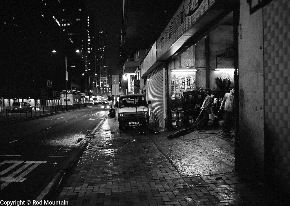 Two young men begin to put away their equipment as they close late into the evening at a local Hong Kong garage.