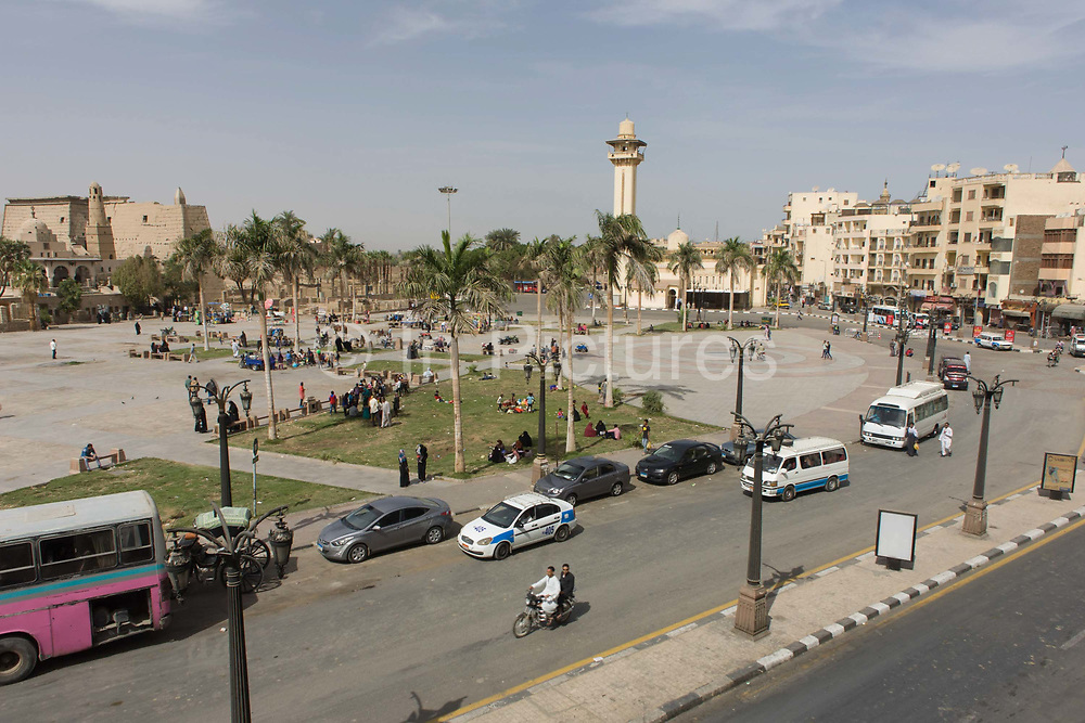 Local traffic in the main square opposite the ancient Egyptian Luxor Temple, Nile Valley, Egypt, seen from a first storey cafe as traffic drives past. An aerial view across the central space used by local familes and passing tourists en route to the temple's first pulon and the lower minaret of Abu el-Haggag's mosque.
