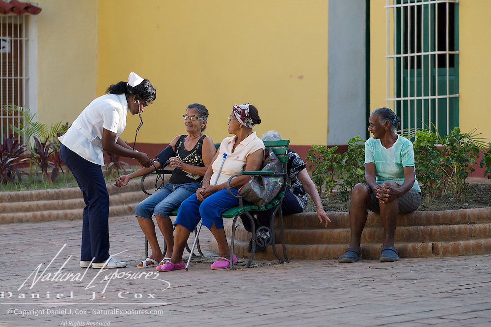 A nurse makes her rounds in the local plaza, helping elderly Cuban residents with their health needs in Trinidad, Cuba.