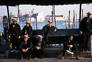 Gondoliers on break, smoking and eating ice cream, on the San Marco Canal, Venice, Italy. The white building behind them is San Giorgio Maggiore basilica designed by Andrea Palladio and located on the island of San Giorgio Maggiore...Subject photograph(s) are copyright Edward McCain. All rights are reserved except those specifically granted by Edward McCain in writing prior to publication...McCain Photography.211 S 4th Avenue.Tucson, AZ 85701-2103.(520) 623-1998.mobile: (520) 990-0999.fax: (520) 623-1190.http://www.mccainphoto.com.edward@mccainphoto.com..edward@mccainphoto.com