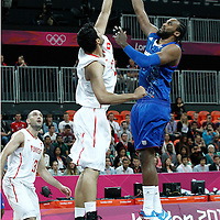 04 August 2012: France Ronny Turiaf goes for the skyhook over Tunisia Mokhtar Ghayaza during 73-69 Team France victory over Team Tunisia, during the men's basketball preliminary, at the Basketball Arena, in London, Great Britain.