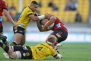 Crusaders Leicester Fainga'anuku tries to escape the tackle of Hurricanes Ngani Laumpae and James Blackwell in the Super Rugby match, Hurricanes v Crusaders, Sky Stadium, Wellington, Sunday, April 11, 2021. Copyright photo: Kerry Marshall / www.photosport.nz