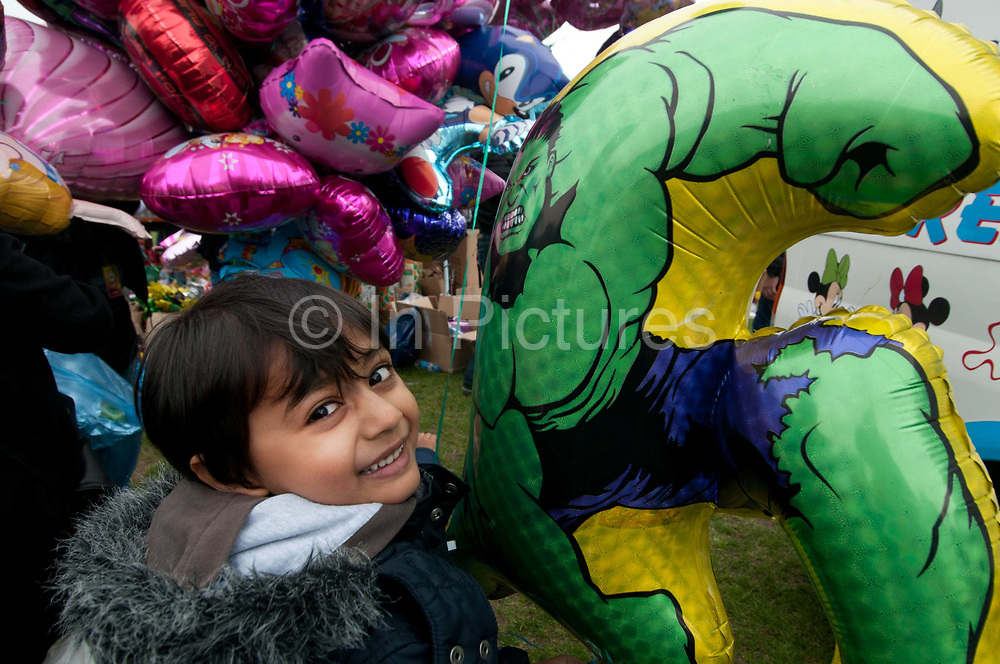 Weavers Fields, Bethnal green, London. Boishakhi Mela, celebration for Bangladesh New Year. Young boy with Incredible Hulk balloon and more balloons in background
