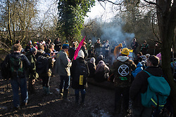 Harefield, UK. 18 January, 2020. Activists from Extinction Rebellion, Stop HS2 and Save the Colne Valley gather around a camp fire as they reoccupy the Colne Valley wildlife protection camp on the second day of a three-day 'Stand for the Trees' protest in the Colne Valley timed to coincide with tree felling work by HS2. Bailiffs acting for HS2 had evicted all but two activists from the camp the previous week. 108 ancient woodlands are set to be destroyed by the high-speed rail link.