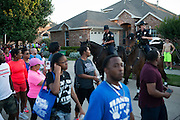 Protesters walk through Craig Ranch North in response to an incident with teens and police officers at a community pool in McKinney, Texas on June 8, 2015.  (Cooper Neill for The New York Times)
