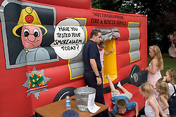 Children playing on bouncy inflatable fire truck at Lark in the Park; West Bridgford; Nottingham,