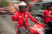 """Mar. 27, 2010 - BANGKOK, THAILAND:  A Red Shirt demonstrator rides a motorcycle through Bangkok March 27. More than 80,000 members of the United Front of Democracy Against Dictatorship (UDD), also known as the """"Red Shirts"""" and their supporters marched through central Bangkok March 27 during a series of protests against and demand the resignation of current Thai Prime Minister Abhisit Vejjajiva and his government. The protest is a continuation of protests the Red Shirts have been holding across Thailand. They support former Prime Minister Thaksin Shinawatra, who was deposed in a coup in 2006 and went into exile rather than go to prison after being convicted on corruption charges. Thaksin is still enormously popular in rural Thailand.    PHOTO BY JACK KURTZ"""