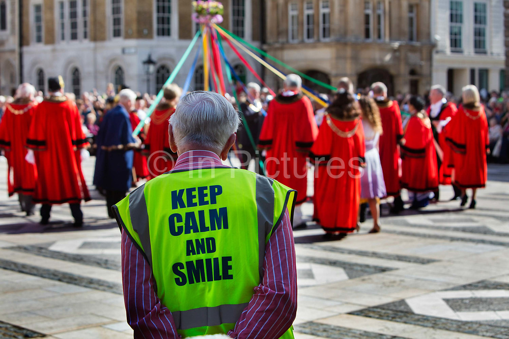 Official wearing a Keep Calm And Smile high vis jacket at the Pearly Kings and Queens Harvest Festival celebrations at Guildhall Yard. The annual event features early English entertainment including maypole dancing, Morris dancers and a marching band. The Chelsea pensioners & all the mayors of London take part in this traditional London event.<br /> The London tradition of the Pearly Kings and Queens began in 1875, by Henry Croft. Inspired by the local Costermongers, a close-knit group of market traders who looked after one another and were recognisable by buttons sewed onto their garments, Henry went out on the streets to collect money for charity, wearing a suit covered in pearl buttons to attract attention. When demand for his help became too much, Henry asked the Costermongers for assistance, many of whom became the first Pearly Families. Today, around 30 Pearly Families continue the tradition to raise money for various charities.