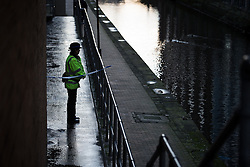 "© Licensed to London News Pictures . Manchester , UK . FILE PICTURE DATED 29/12/2013 of a PCSO standing behind police tape adjacent to the River Medlock off Oxford Road in Manchester City Centre . The search for a 17 year old from Stockport , who was last seen in the early hours of Saturday 28th December in Manchester City Centre following a night out with friends . Greater Manchester Police have issued a statement after suggestions that a number of deaths in and around Manchester's canals may be linked to a serial killer , named in local folklore as "" The Pusher "" . The statement said "" Absolutely no evidence whatsoever of foul play has been established "" . Photo credit : Joel Goodman/LNP"