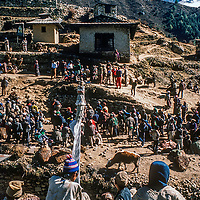 Traders and Village farmers who have trekked days from lowland Nepal sell their  wares  at  the Saturday bazar in mountainous Namche Bazaar, leading town of the Sherpa people. Thamserku Peak rises behind.