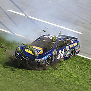 Race car driver Chase Elliott (24) slides across the grass in the front stretch during the 58th Annual NASCAR Daytona 500 auto race at Daytona International Speedway on Sunday, February 21, 2016 in Daytona Beach, Florida.  (Alex Menendez via AP)