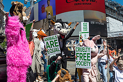 """© Licensed to London News Pictures. 16/06/2021. LONDON, UK.  People wearing animal costumes at an anti-animal cruelty protest at Piccadilly Circus, supported by fashion designer Stella McCartney, encouraging the public to sign the HSI Fur Free Britain petition.  The message """"Our Time Has Come"""", from McCartney's Autumn 2021 campaign, is displayed on the big screens behind them.  Photo credit: Stephen Chung/LNP"""
