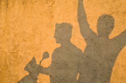 Shadow On A Wall Of Two People On A Moped