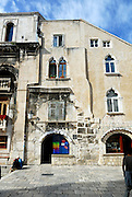 "Section of wall in Peristyle, with ancient arch, shuttered windows, Gothic arched windows, and ""na koljeno"" style of door/window/counter. Diocletian Palace, Split, Croatia"